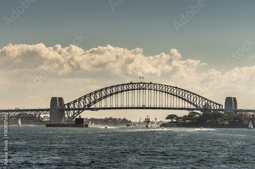 Sydney, Australia - March 26, 2017: Frontal view of black metalic Harbour Bridge including support towers on both sided seen off water under cloudscape. Denison Fort in bay and multiple small boats.