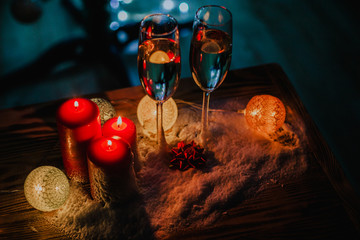 Two glasses of champagne on the background of a Christmas tree with candles in darkness with snow