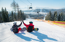 Snowboarders Sit On The Top Of...