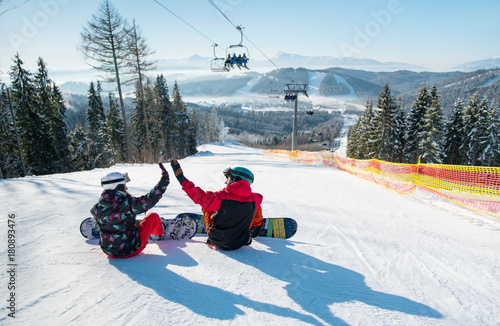 fototapeta na ścianę Snowboarders sit on the top of the ski slope under the ski lift let's high five to each other with a beautiful scenery of mountains and forests on a sunny morning