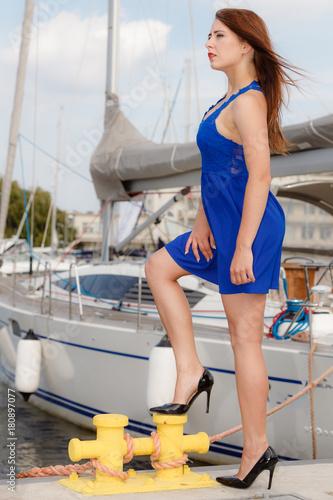 Dominant feminist woman wearing high heels in marina
