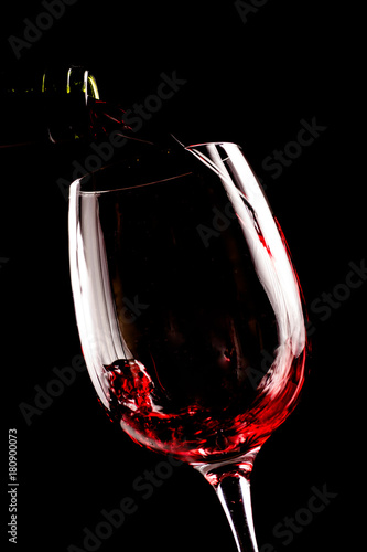 Red wine pouring in wineglass from a bottle on black background. Wine list design menu with copyspace.
