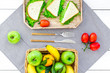 Healthy food for picnic. Sanwiches, fruits, vegetables on tablecloth on white wooden background top view