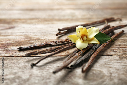 Fotografía  Dried vanilla pods and flower on wooden background