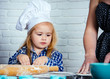 Child cook in chef hat helping mother