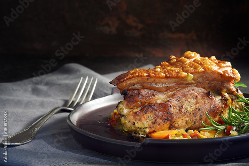 juicy roast pork with crunchy crust, rosemary and vegetables on a gray napkin against a rustic dark background, moody light, copy space
