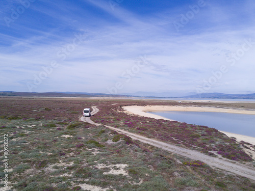 Photo  White Campervan Driving on a single Road Track in northern Spain