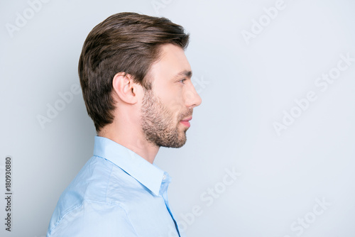 Valokuva  Close up side portrait of young bearded manager standing over grey background wi