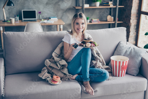 Typical woman weakness! Extremely happy woman is going to watch her favourite TV serials, eat donuts and popcorn on holiday