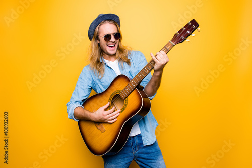 Music is my lifestyle! Excited and carefree musician dressed in casual clothes and spectacles playing the acoustic guitar and singing a song - 180932603