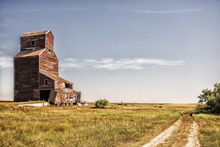 An Abandoned Old Crumbling Tall Wooden Grain Storage Elevator Surrounded By Agriculture Crops In A Desaturated Rural Countryside Summer Landscape