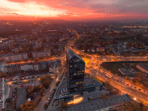 Fototapeta Modern architecture office building, Transportation, rush hour traffic, cars on highway interchange in city center. Sunset time, orange and gold light skyline. Drone aerial view of Krakow, Poland.  obraz