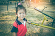 Asian child standing near seesaw at children playground. Vintage tone.