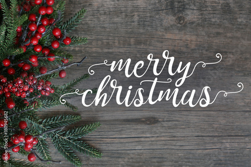 Fotografie, Obraz  Merry Christmas Text with Evergreen Branches and Berries Over Dark Rustic Wood B