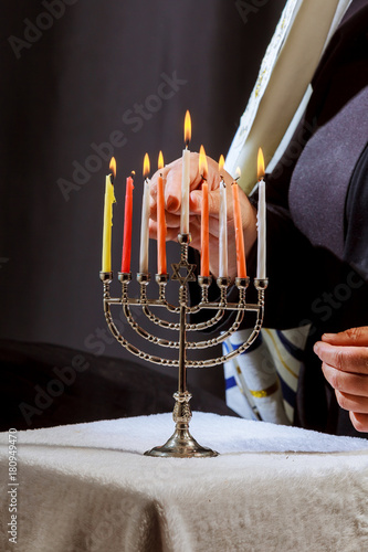 Lighting Menoral Candles man hand lighting candles in menorah on table served fo Canvas Print