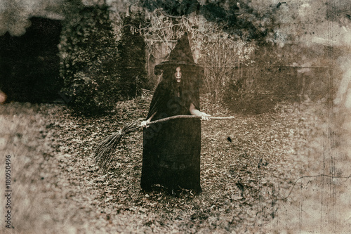Fotografie, Obraz  Insidious witch holding a broom in a rural setting, heavily edited with vintage film effects