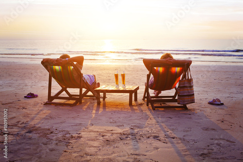 Carta da parati honeymoon travel, silhouettes of happy couple relaxing in deck chairs on the bea