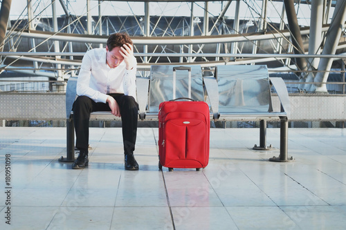 Fotografie, Obraz  flight delay or problem in the airport, tired desperate passenger waiting in the