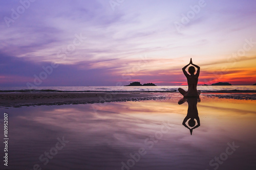 mindful meditation background, silhouette of woman doing yoga on the beach at su Canvas Print