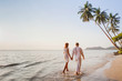canvas print picture - romantic young couple walking together on beautiful exotic tropical beach at sunset