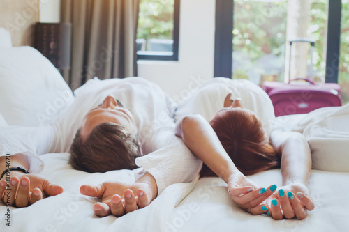 hotel guests relaxing on the bed in their room, couple traveling to luxurious resort