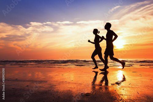 Obraz running background, sport and workout, silhouettes of people jogging at sunset beach - fototapety do salonu