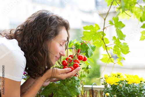 Fotografia Young woman taking care of her plants and vegetables on her city balcony garden