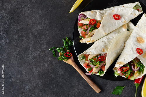 Mexican tacos with filling and guacamole sauce on a black background