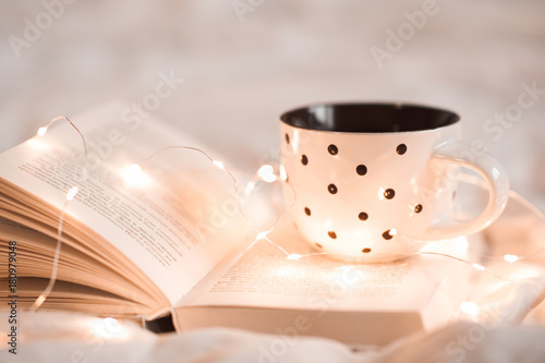 Cup of tea staying on open book with Christmas lights in bed closeup