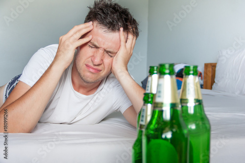 Fényképezés  Hangover suffering man holding his aching head close up portrait with bottles of beer