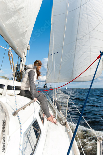 Poster Zeilen Young girl having trip on sailing yacht in windy sea