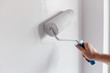 Leinwanddruck Bild - Male hand painting wall with paint roller. Painting apartment, renovating with white color paint