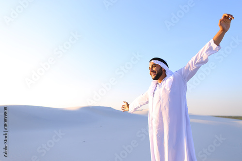 Poster Abou Dabi Happy Muslim guy walks through expanses of desert and rests with