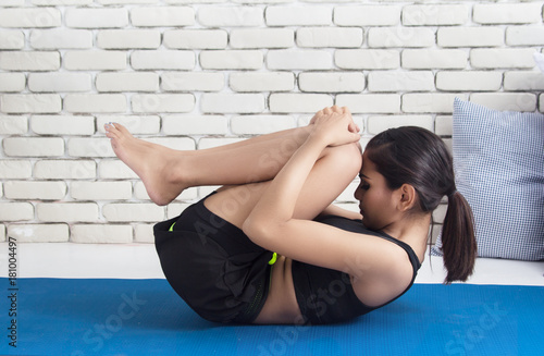 The lady in exeThe lady in black exercise suit is posing easy yoga,the name  of this pose is Knees to Chest Pose, at home,blurry light background.rcise  is posing yoga at home. -