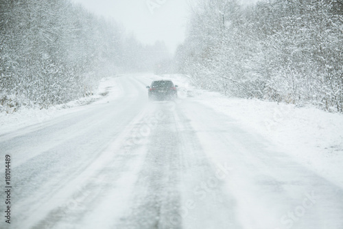 Fotografia The car is driving on a winter road in a blizzard