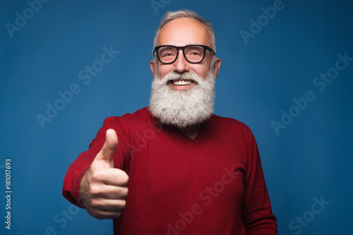 Fototapeta Happy modern old bearded man in warm sweeter show thumb up and happy smiling
