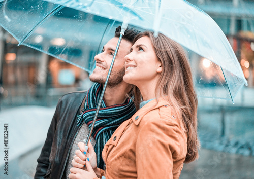 Photo  Young happy couple under the rain day covering with transparent umbrella in city