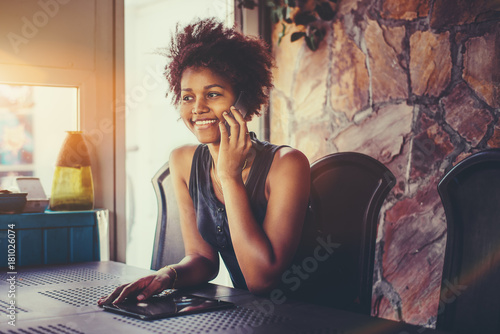 Valokuva  Smiling attractive young African American girl with curly hair is sitting in dar