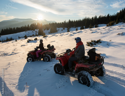 Young couple riders sitting on four-wheelers ATV bikes on snow, enjoying sunset in the the mountains in winter
