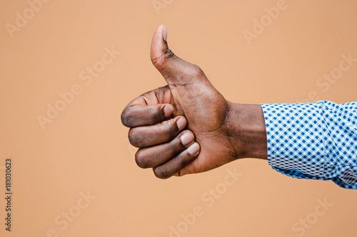 Fotografía  Hand showing OK sign isolated on brown background.