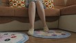 The feet of the sitting woman in woolly knitted socks. Braided rug