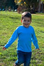 Joyful Little Boy Having Fun While Running In The Park.