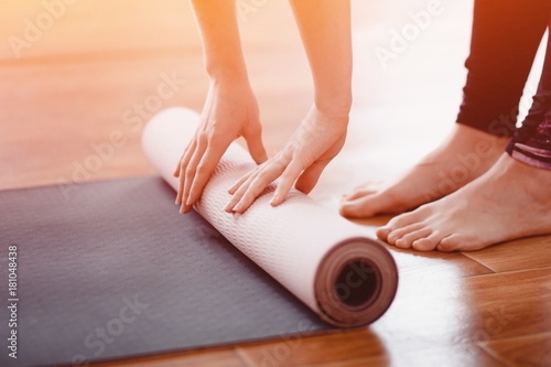 Obraz Yoga. Close-up woman folding roll fitness or yoga mat after working out home in living room. Concept healthy life. - fototapety do salonu