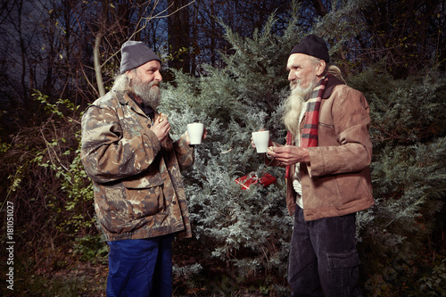 Two Homeless Older Men Celebrating Christmas In Park With Gifts