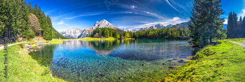 Photo Stands Lake Arnisee with Swiss Alps. Arnisee is a reservoir in the Canton of Uri, Switzerland.