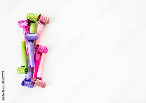 vertical border row of colorful new years eve noisemakers isolated on white
