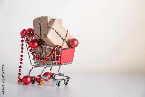 Fototapeta Christmas shopping, gift boxes in kraft paper and red baubles in a shopping cart or trolley on a light background with copy space obraz