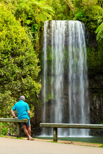 Man Standing In Front Of Milla Milla Falls (Australia)