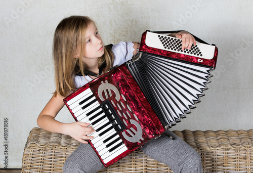 Fototapeta Close up of a girl accordionist focused on playing the accordion