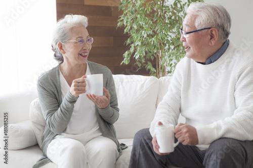 Obraz An old couple enjoying friendship tea time - fototapety do salonu